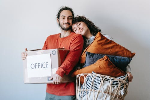 Man Carrying A Box And Woman With Throw Pillows In A Basket