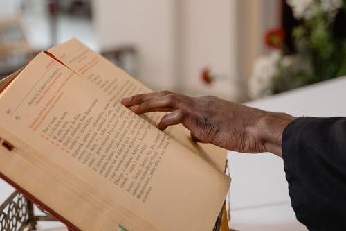 Close-Up View of a Person Touching a Bible