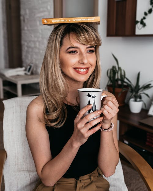 Cheerful female with mug of beverage and textbook on head looking forward while sitting in armchair in house room
