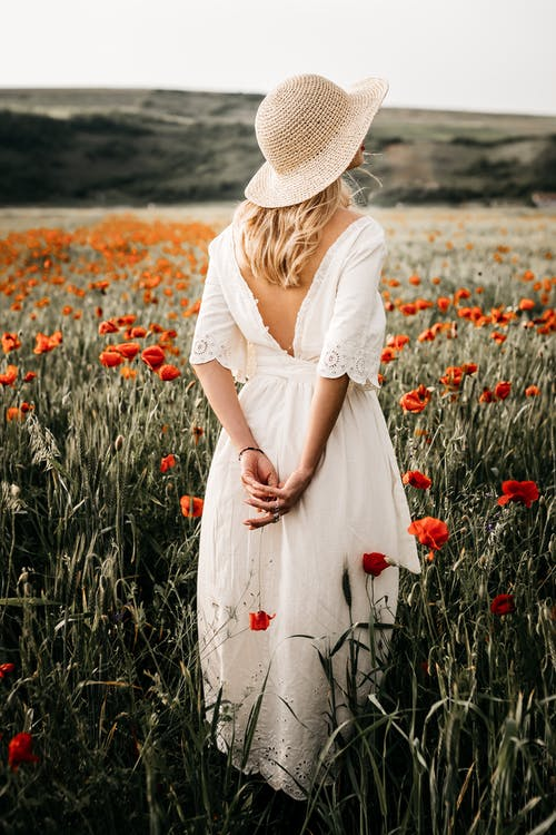 Back view of anonymous female in hat admiring hills while standing with hands behind back on meadow with blooming flowers