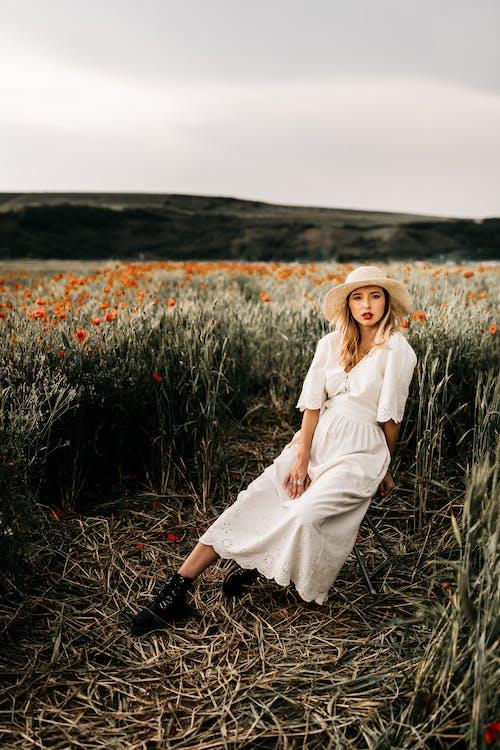 Stylish model in white dress in countryside field