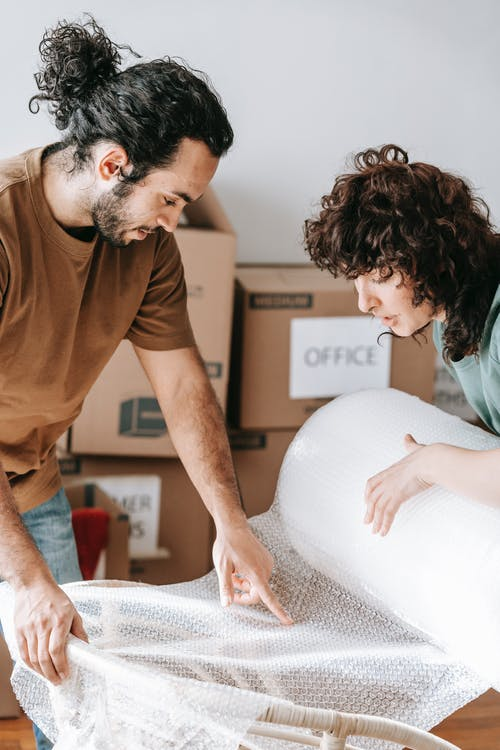 Couple Holding A Roll Of Bubble Wrap