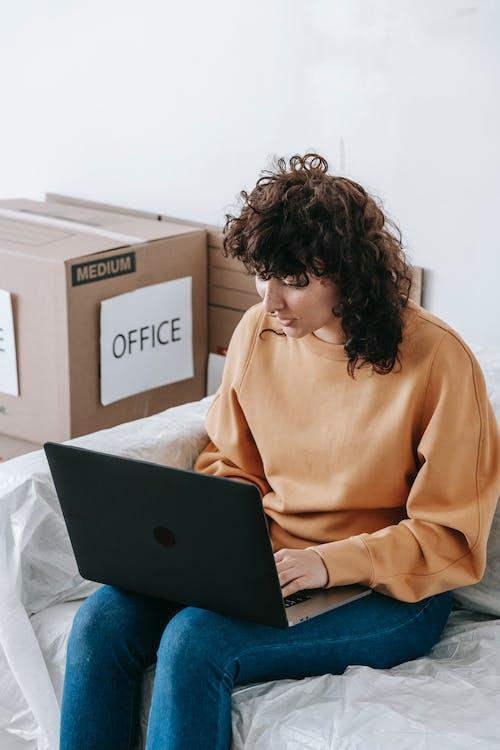 Woman In Orange Sweat Shirt Using Laptop