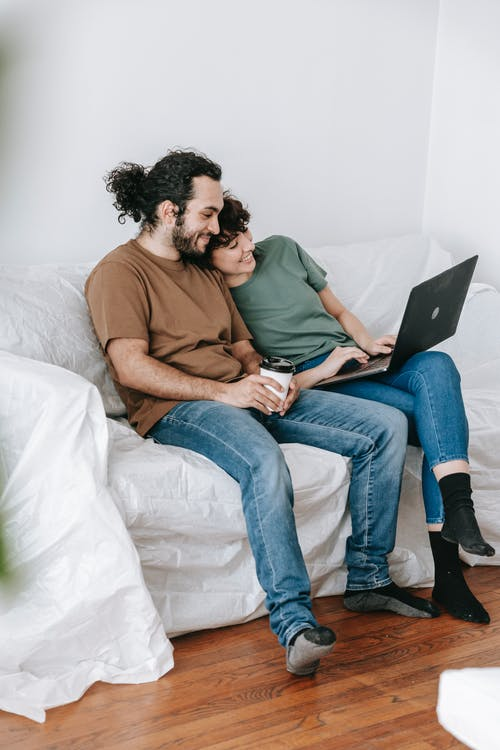 Couple Sitting On A Couch Using A Laptop