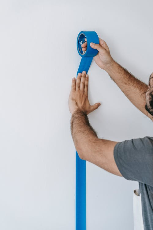 Crop Photo Of Man Putting Tape On Wall