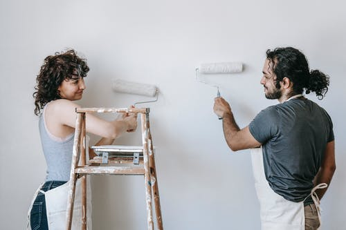 Smiling ethnic couple painting wall with roller brushes at home