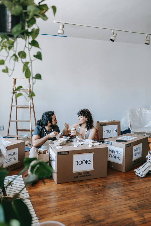 Couple Eating On Packed Boxes In A Room