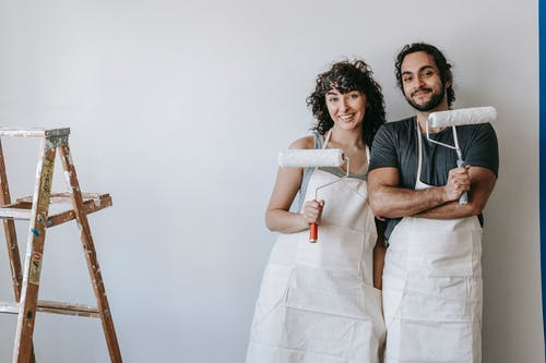 Couple Standing Against The Wall Holding Paint Rollers