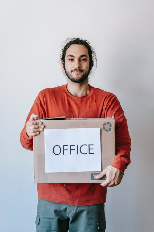 A man carrying a box labelled as 'office'.