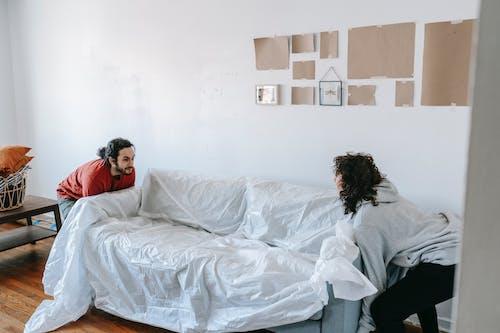 A Couple Lifting A Sofa