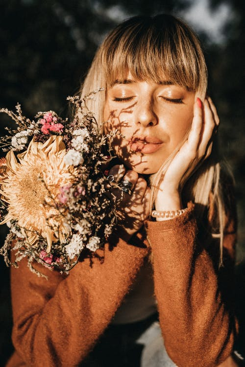 Young mindful female with closed eyes and blossoming flowers touching cheek in soft sunlight on blurred background