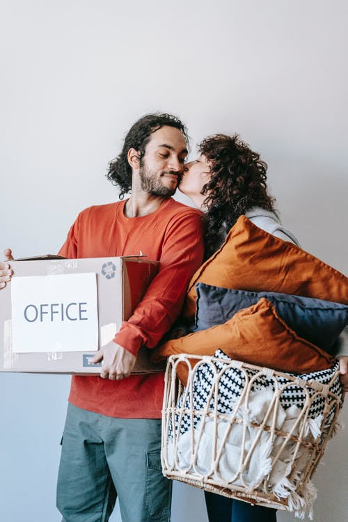 Woman Kissing A Man Carrying A Box Of Packed Office Supplies