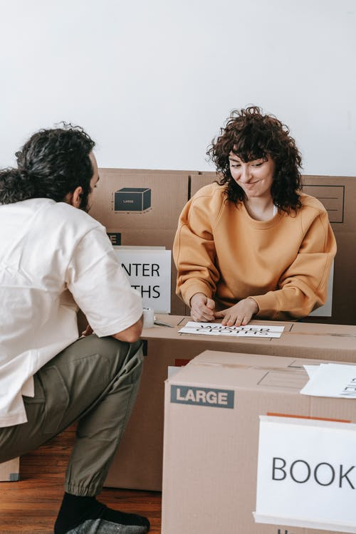A Couple Packing Things In Boxes