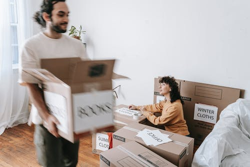 Couple Packing Things In Boxes