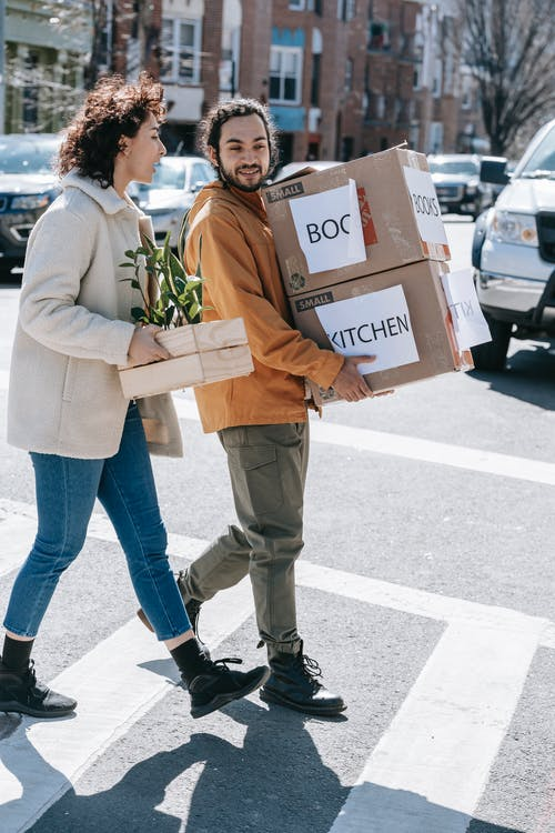 Couple Walking Along The Street Carrying Boxes And Plants