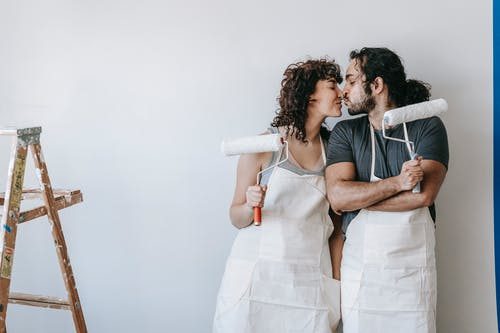 Couple Holding Paint Rollers And Kissing