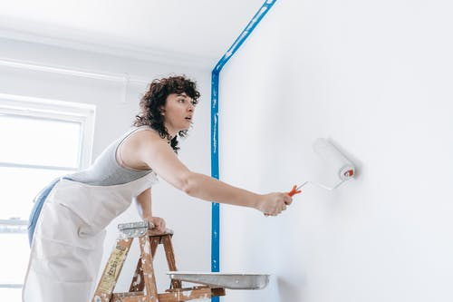 Woman Painting The Wall With A Roller Brush