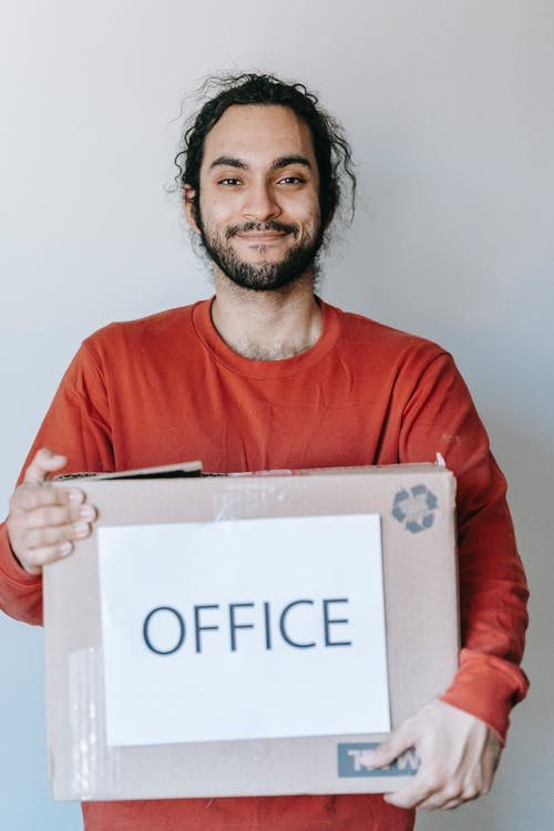 Man Carrying A Box With Office Sign