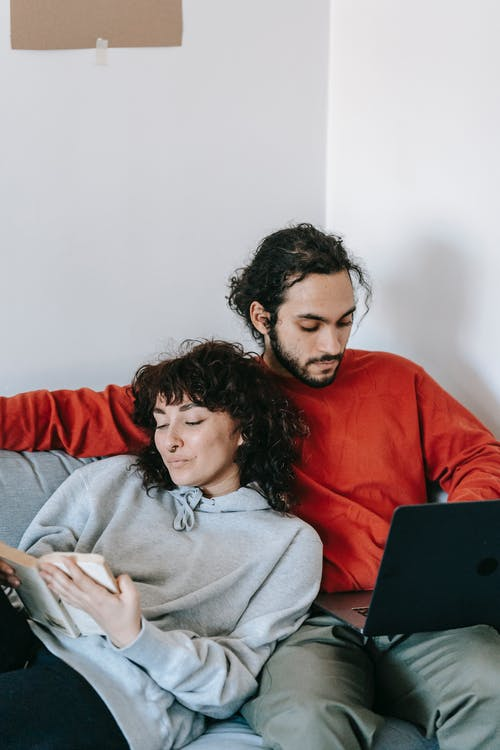Ethnic couple with laptop and book resting on sofa
