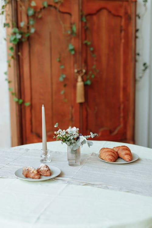 Two Plates of Croissants beside a Candle on a Table