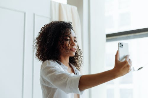 Close-Up Shot of an Afro-Haired Woman Taking Selfie Using a Smartphone
