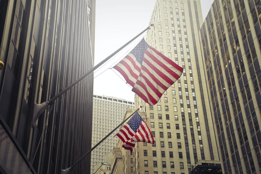 Two U.s.a. Flags Under White Clouds at Daytime