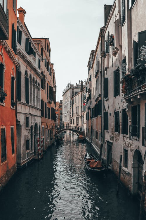 Bridge above rippled water channel with boats between aged stone building exteriors in Venice Italy