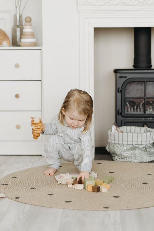 Girl in Gray Sweater Playing With White and Yellow Plastic Toy