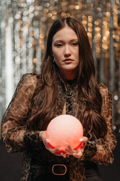 Woman in Black See-Through Top Holding a Glowing Sphere