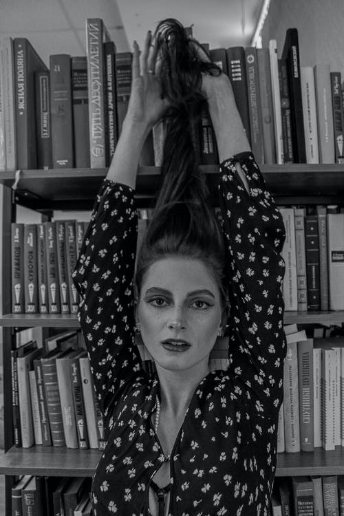 Feminine woman with long hair in library