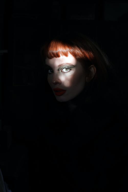 Young female with eyeshadow on eyelid and red hair with bang looking at camera in sun ray on black background