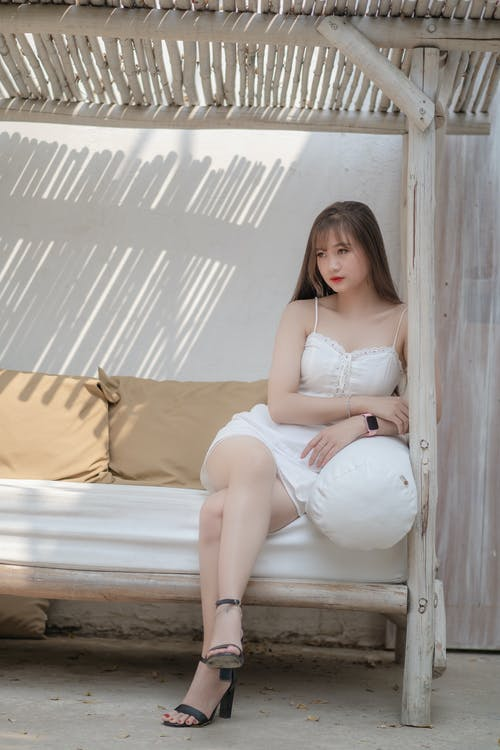 Woman in White Lingerie Sitting on Brown Bed