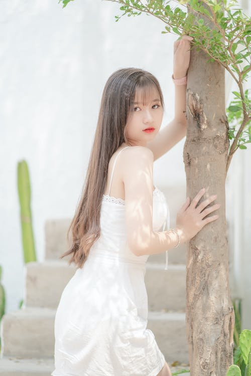 Girl in White Dress Leaning on Brown Tree