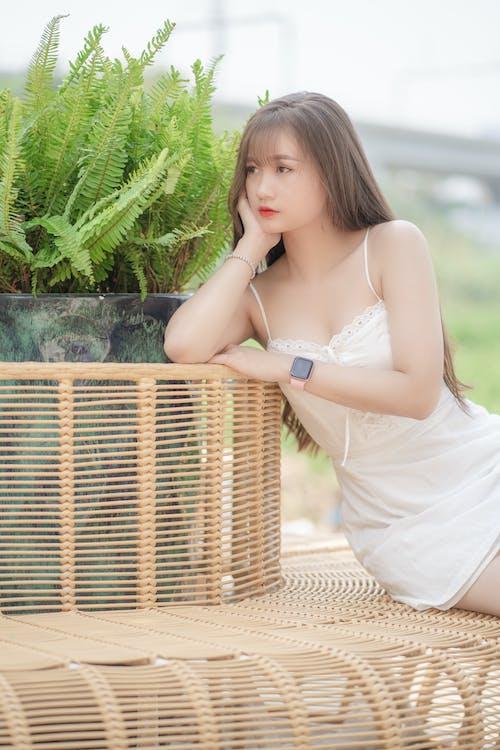Woman in White Spaghetti Strap Dress Holding Brown Woven Basket