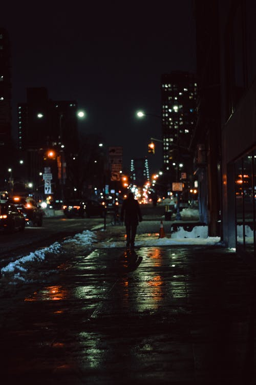 Wet snowy street of modern city district at night