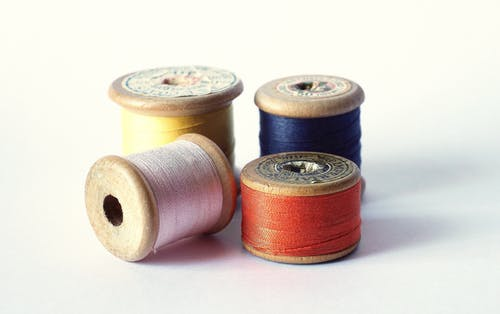 Brown Thread Roll on White Surface