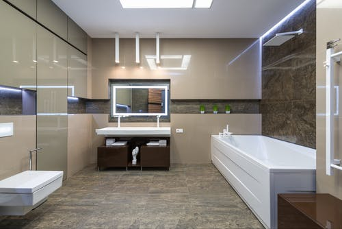 White bath placed near sink with mirror in light spacious bathroom with sink and toilet in modern bathroom with apartment