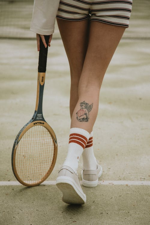 Woman in White and Red Socks and White Shoes Holding Brown and Black Tennis Racket