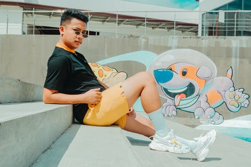 Side view of confident young Asian guy in trendy outfit and sunglasses leaning on hands while resting on stone steps near creative graffiti wall on sunny day in city