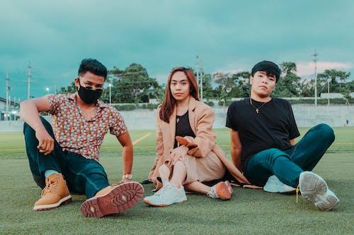 Asian friends sitting on grass in stadium
