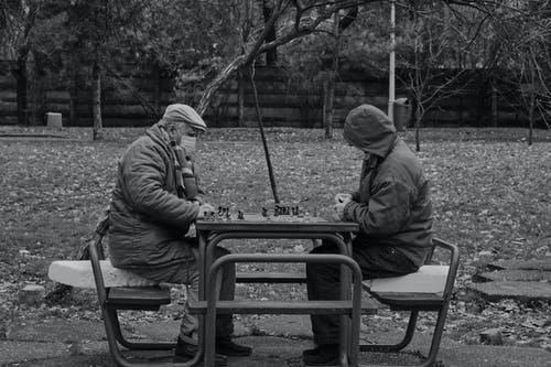 Grayscale Photo of Two People Playing Chess