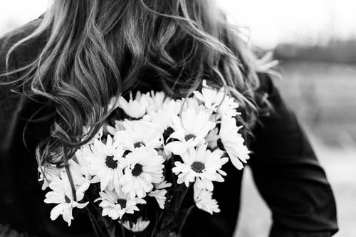 Grayscale Photo of Woman With Blonde Hair With White Flowers