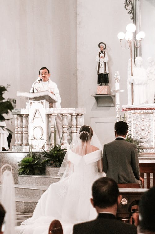 Groom with bride and guests listening to speech of priest standing behind podium in church during wedding ceremony