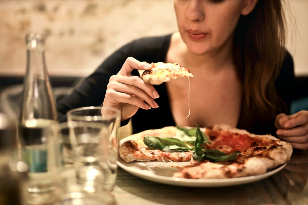 Woman eating a pizza. | Photo: Pexels