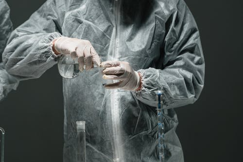 Person in Medical PPE Holding a Flask