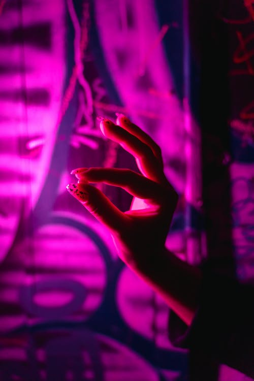 Persons Hand on Purple and Blue Light