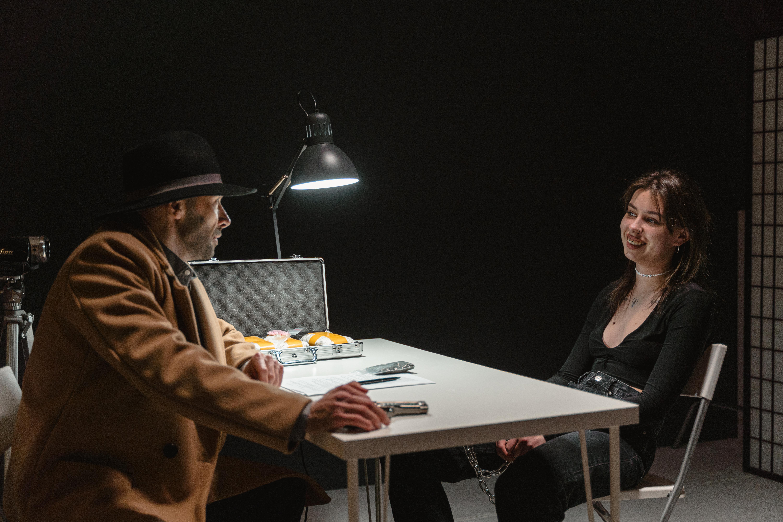 woman in brown coat sitting beside woman in black shirt
