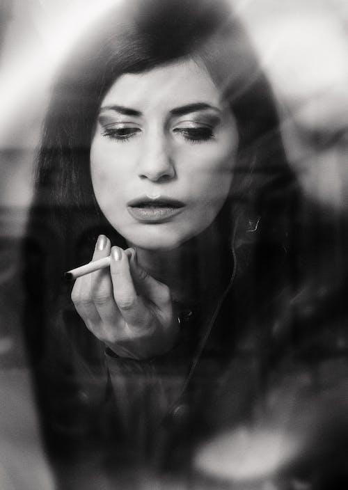 Pensive woman with makeup smoking cigarette