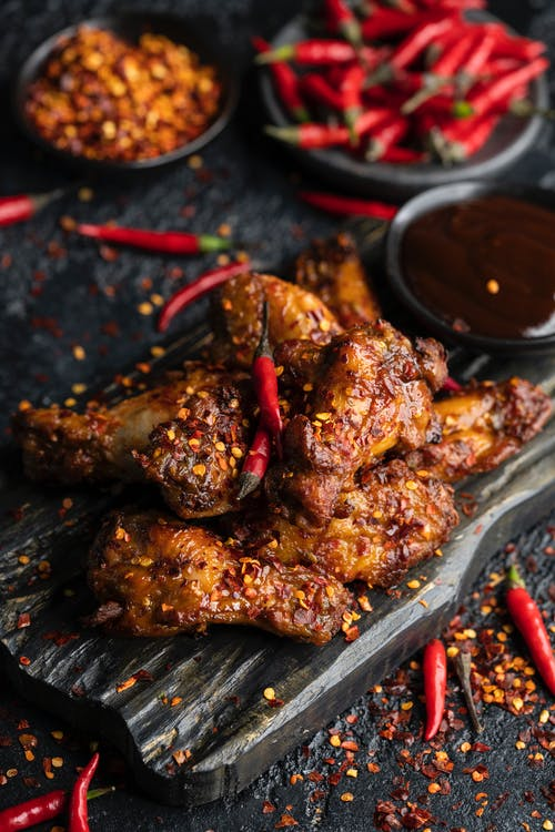 Cooked Meat with Chilies on Wooden Surface