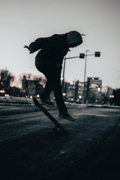 Person in Black Hoodie Jacket Skateboarding